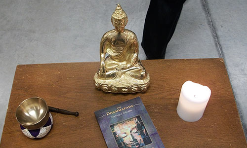Buddha statue and candle around which the sangha gathers